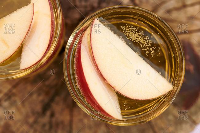 Sparkling apple cider served with apple slices on tree stump