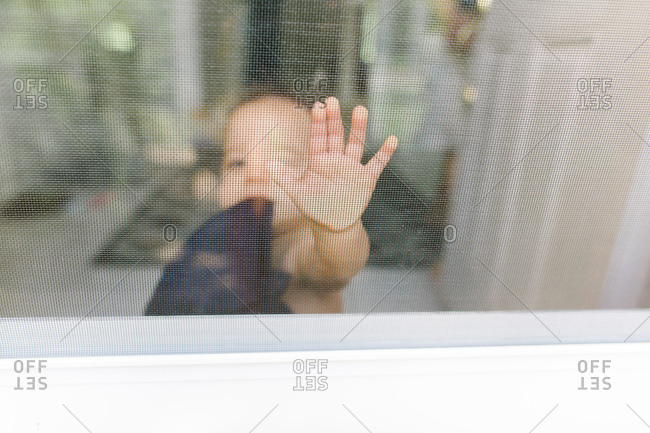 Baby pressing hand against window screen