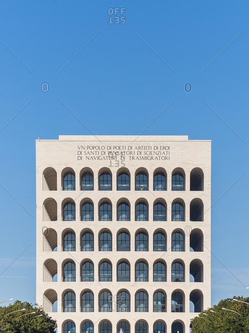 Rome, Italy - November 21, 2016: Exterior of a historic multi-story building, the Palazzo della Civilta Italiana, with arched windows against blue sky