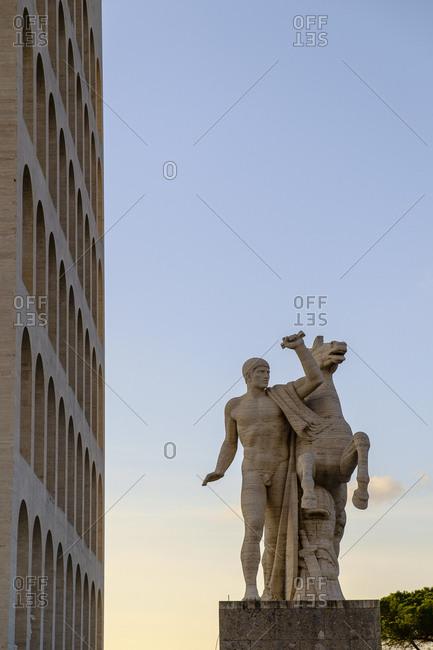 Rome, Italy - February 11, 2012: Sunset view of a statue and the Palazzo della Civilta Italiana
