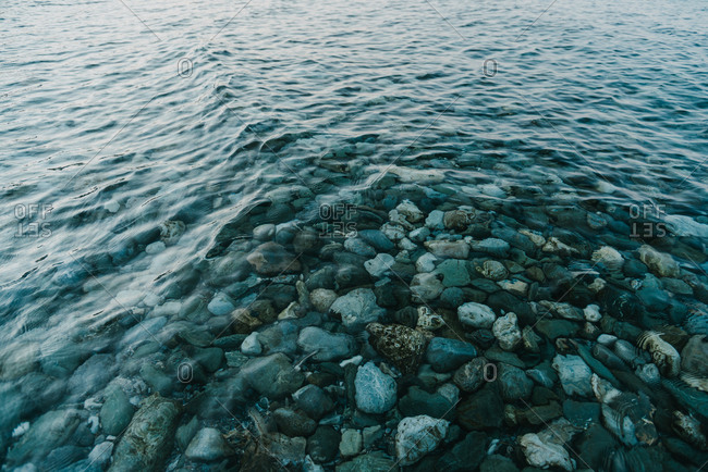 View of clear peaceful sea water and little rocks