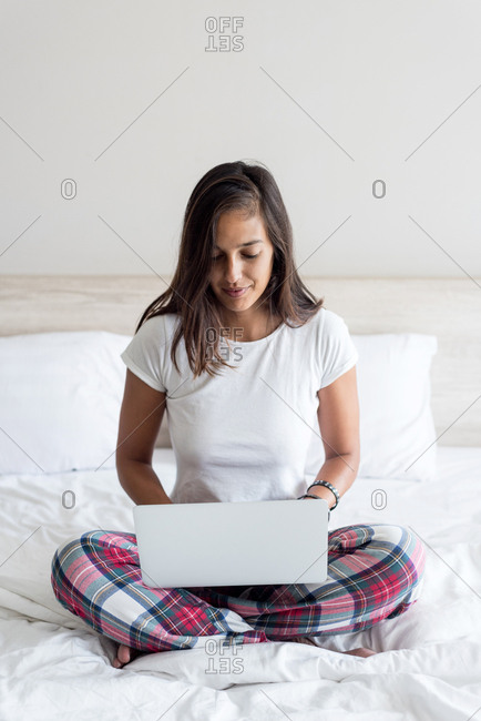 Young woman work with her laptop in her bed