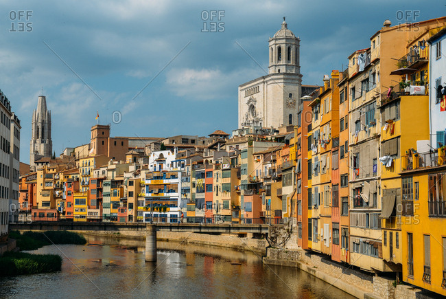 July 10, 2018: Colorful houses on the embankment of the River Onyar in historic center with Girona's Cathedral in the background on right, Girona, Catalonia, Spain, Europe