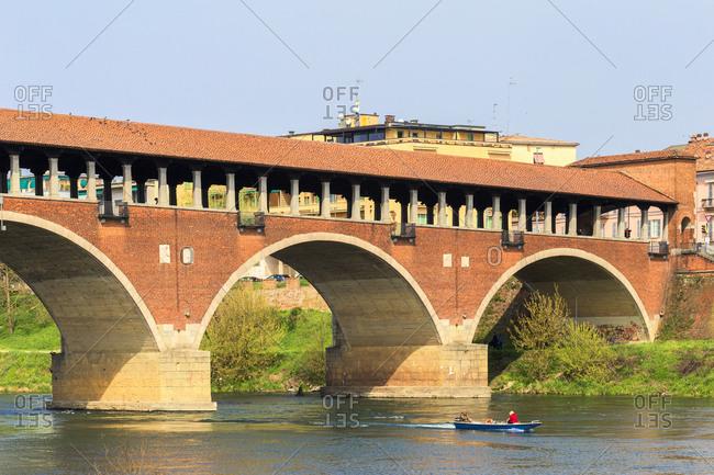 A boat navigates under the Ponte Coperto, Pavia, Pavia province, Lombardy, Italy, Europe