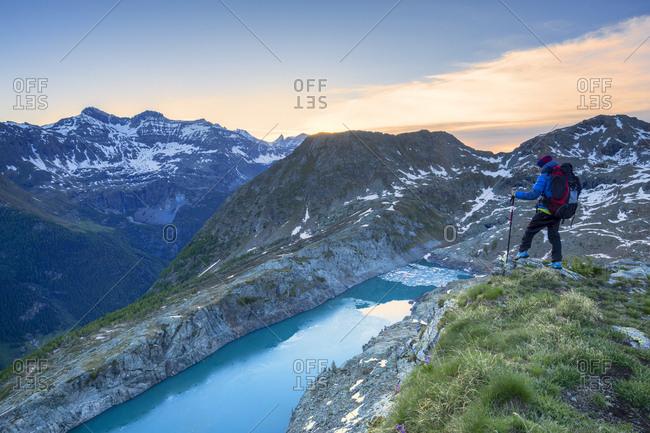 June 9, 2018: A hiker looks at Lake Pirola from above at sunrise, Chiareggio valley, Valmalenco, Valtellina, Lombardy, Italy, Europe