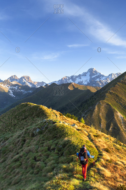Hiker walks on the ridge of Mount Rolla with Mount Disgrazia in the background, Valtellina, Lombardy, Italy, Europe