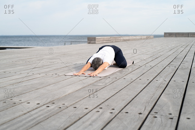 Middle-aged woman stretching on yoga mat by ocean