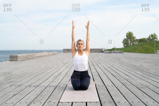 Middle-aged woman stretching arms up to the sky on yoga mat by ocean