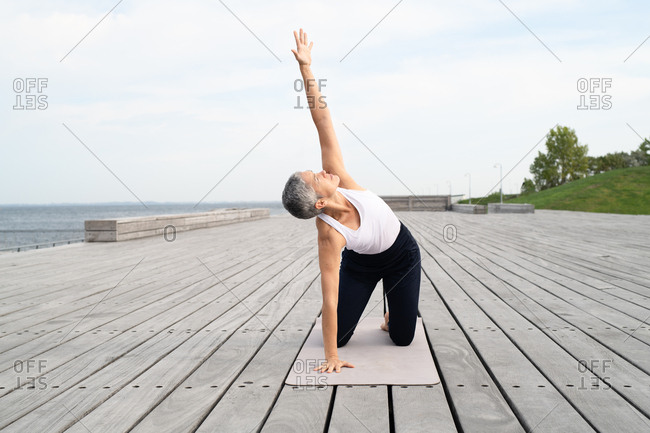 Middle-aged woman stretching her arm up to the sky on yoga mat by ocean