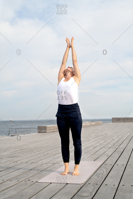 Middle-aged woman stretching arms up to the sky while standing on yoga mat