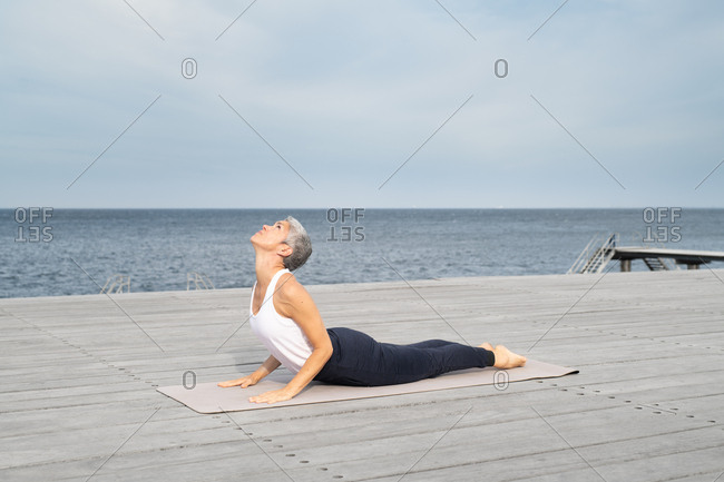 Middle-aged woman doing cobra pose on yoga mat by ocean