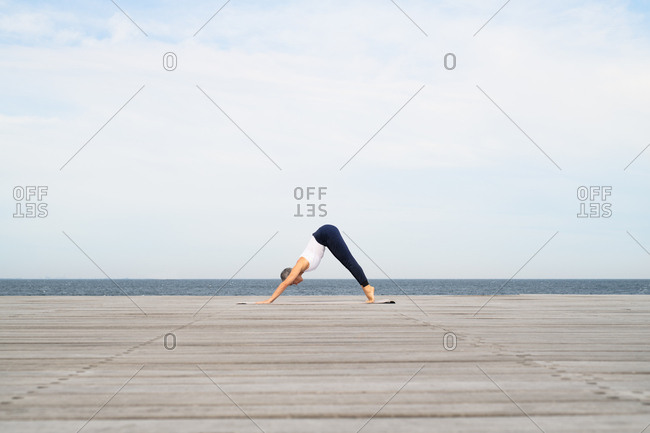 Middle-aged woman doing downward dog pose on yoga mat by ocean