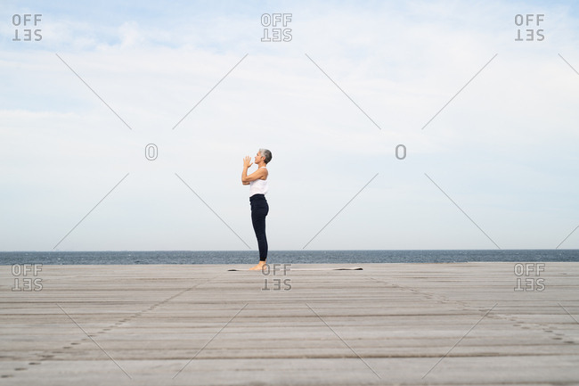 Middle-aged woman standing on yoga mat by the ocean