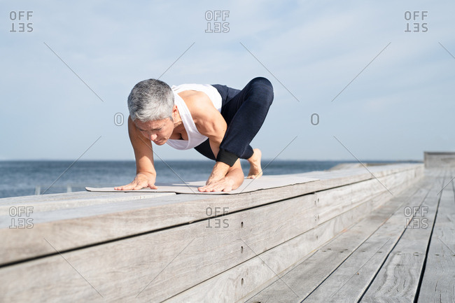 Middle-aged woman doing yoga by the sea