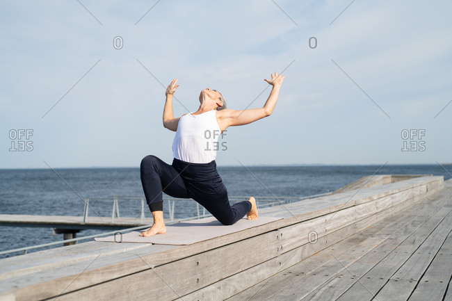 Middle-aged woman doing yoga by the ocean