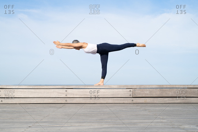 Middle-aged woman doing warrior three yoga pose by the sea