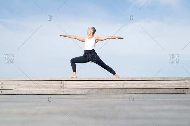Middle-aged woman doing warrior two yoga pose by the sea