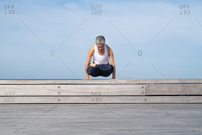 Middle-aged woman doing scales pose while doing yoga by ocean