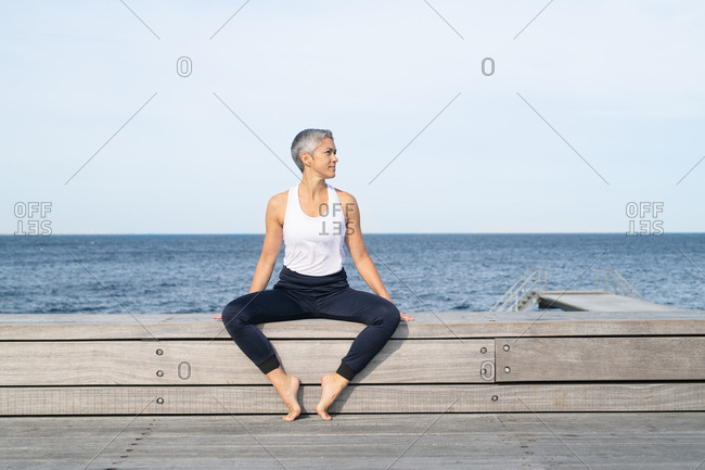 Middle-aged woman taking break while doing yoga by ocean