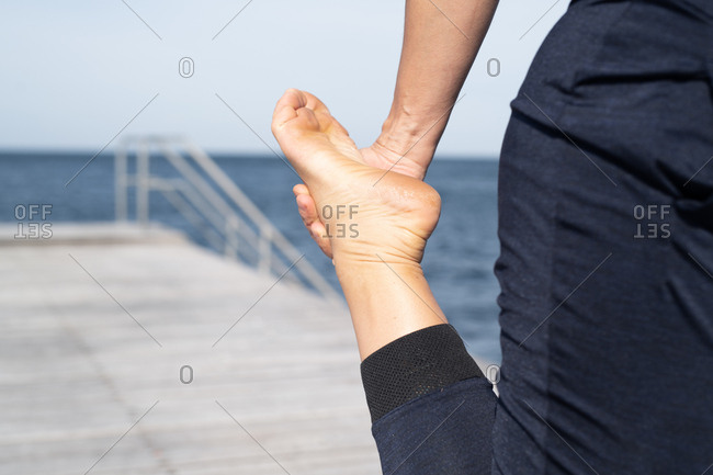 Woman stretching her leg during workout by ocean