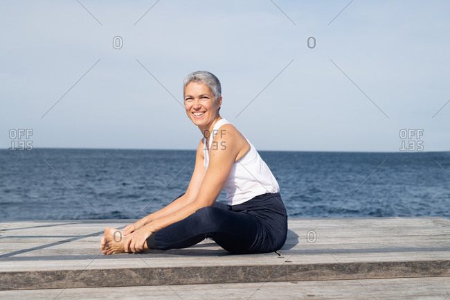 Middle-aged woman stretching by ocean