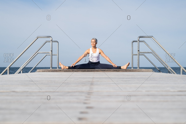 Middle-aged woman stretching legs by ocean