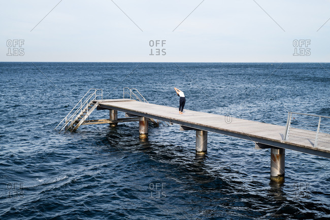 Middle-aged woman stretching on ocean pier