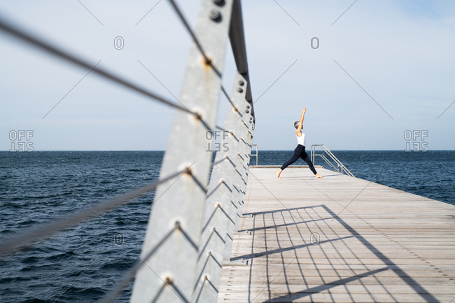 Middle-aged woman doing warrior yoga pose by the sea