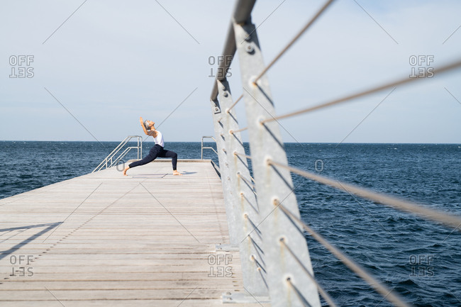 Middle-aged woman doing yoga pose on ocean pier