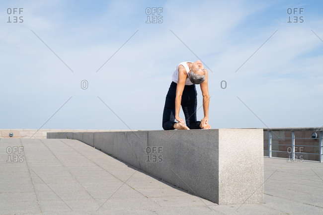 Middle-aged woman stretching on stone wall