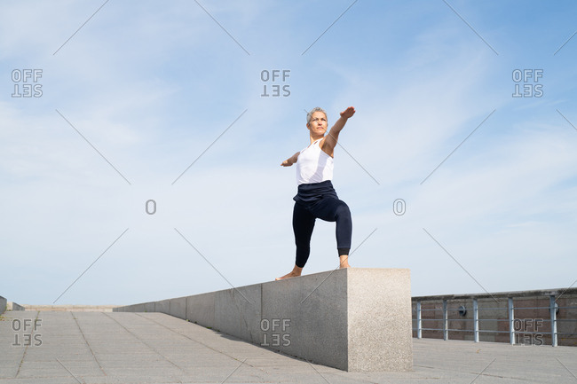 Middle-aged woman doing warrior two yoga pose on stone wall