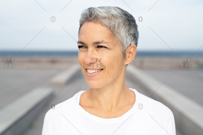 Portrait of a smiling middle-aged woman by the ocean looking away