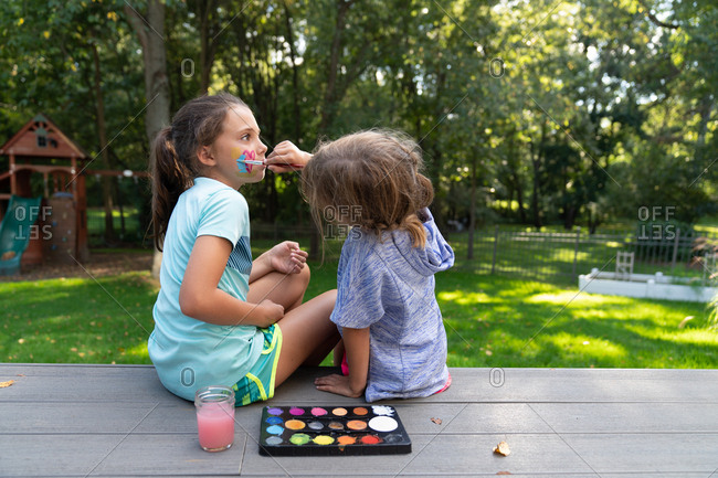 Little girl painting her sister's face in backyard