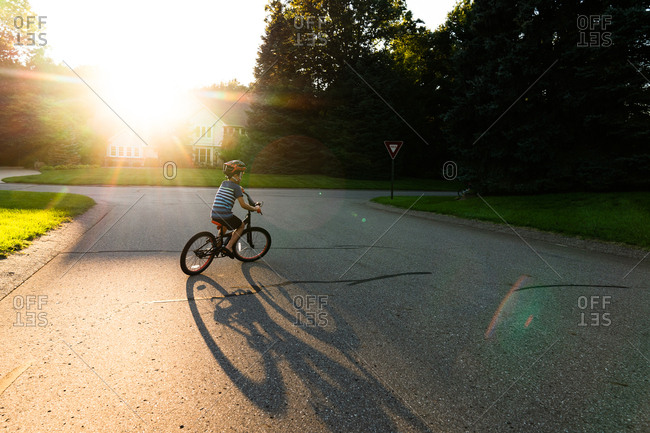 Boy riding bike on street with lens flare