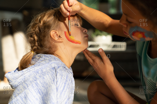 Girl painting rainbow on her sister's face