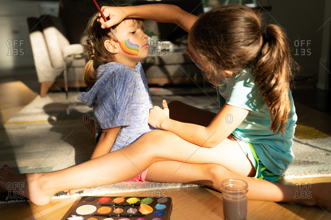 Girl painting a rainbow on her little sister's face