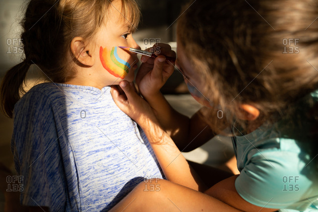 Girl painting rainbow on her little sister's face