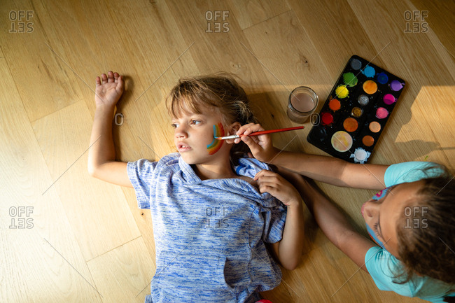 Overhead view of girl painting a rainbow on her little sister's face