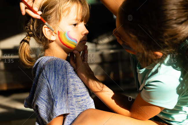 Young girl painting rainbow on her little sister's face