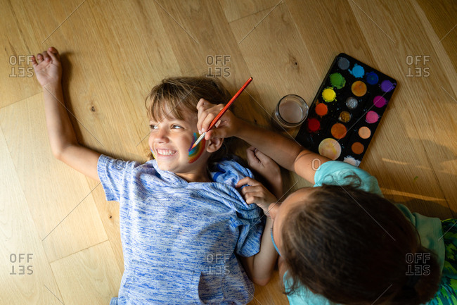 High angle view of girl painting a rainbow on her little sister's face