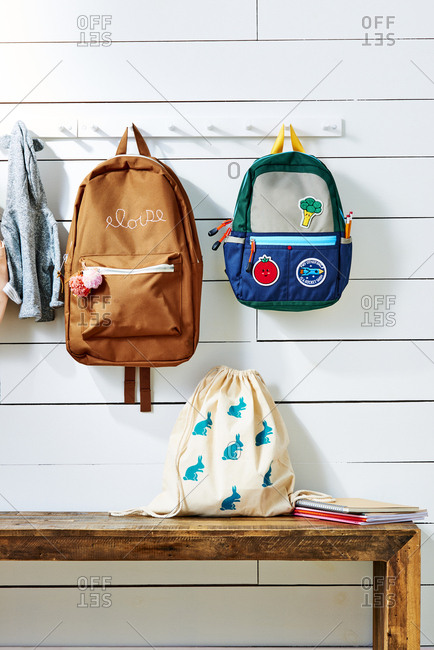 Personalized school bags hanging on wall-mounted rack