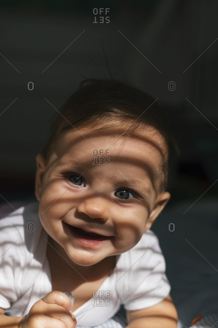 Portrait of a smiling baby in shadows from window blinds