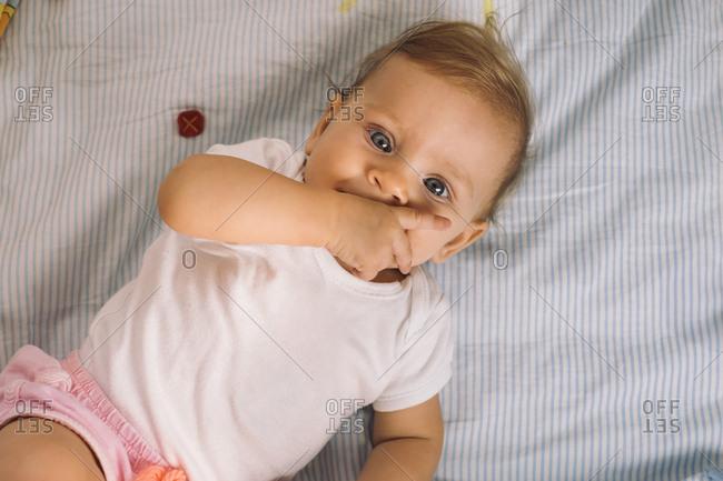 Baby lying in crib and sucking thumb