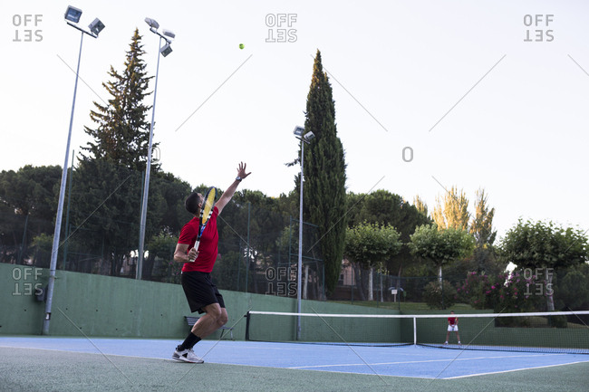 Man throwing up ball and aiming for it while playing tennis on court