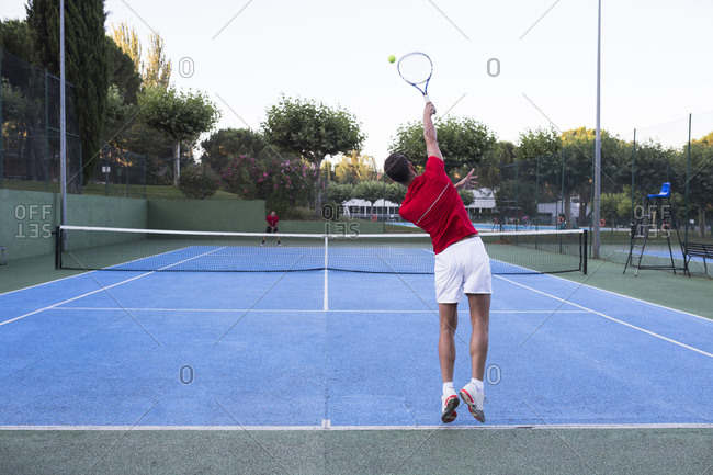 Man hitting ball with power while playing tennis on court