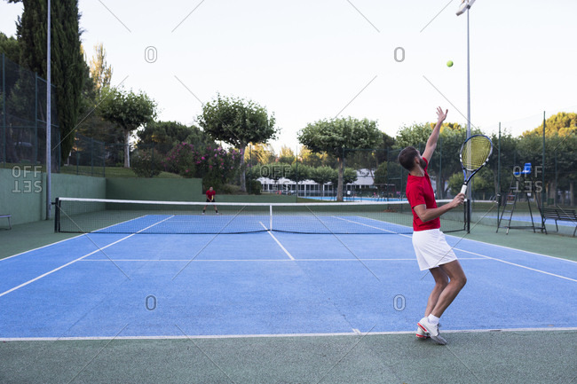 Man throwing up ball and aiming for it while playing tennis