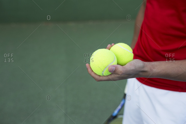 Unrecognizable sportsman holding two balls while standing on tennis court