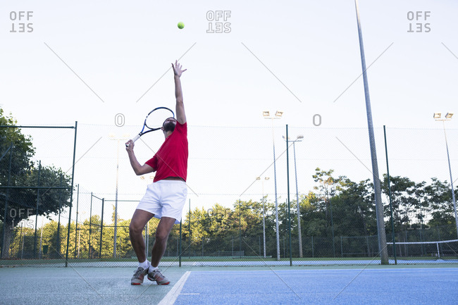 Man throwing up ball and aiming it while playing tennis on court