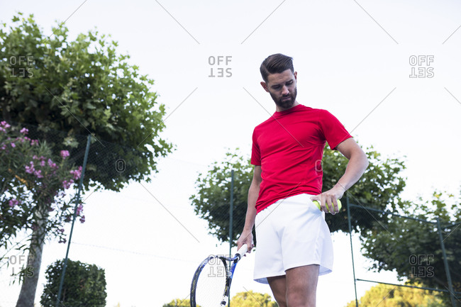 Handsome bearded guy holding racket and looking down while standing on tennis court