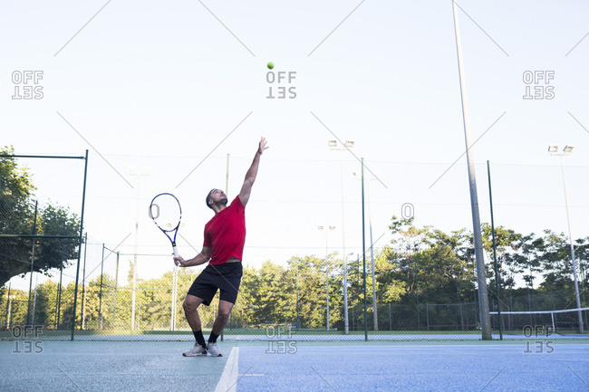 Guy throwing up ball and aiming for it while playing tennis on court